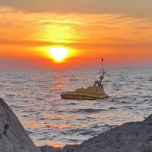 Autonomous vessel under a bright yellow sunrise