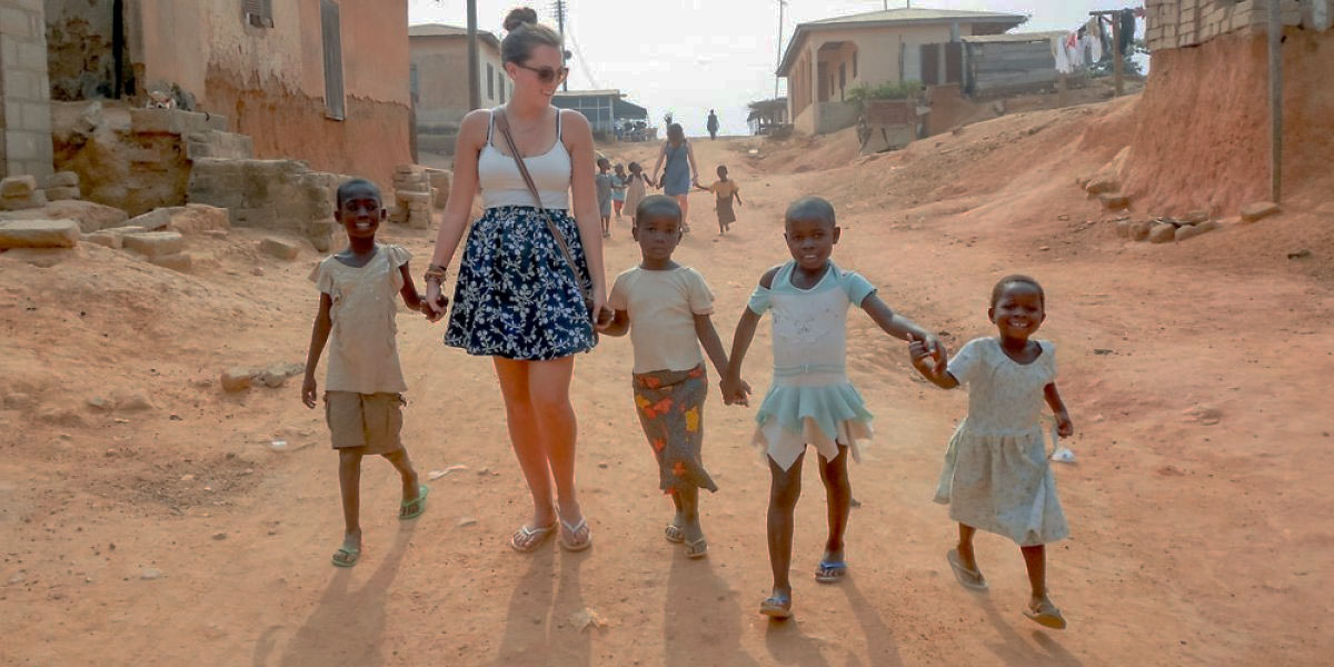 Student walking with native children