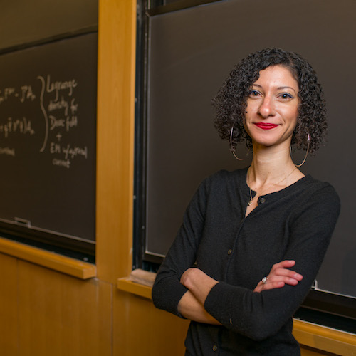 Female professor stands with arms crossed in front of chalkboard