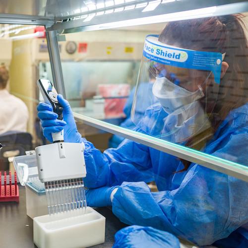 Technician in full protective gear runs COVID PCR tests