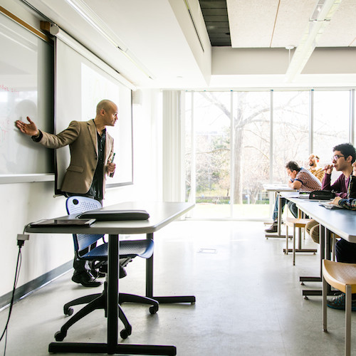 Professor at white board in front of students
