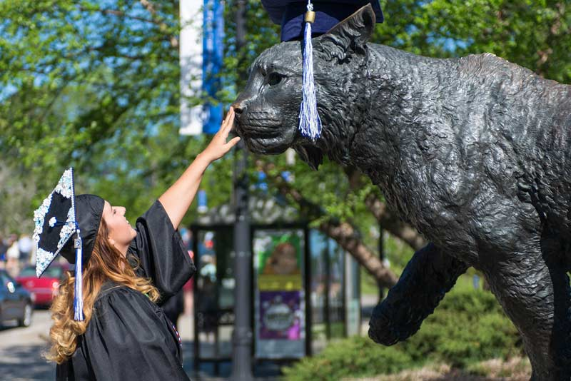 unh student and wildcat statue