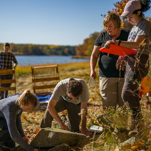 Small group of archaeologists work at edge of Great Bay