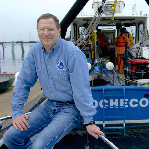 Larry Mayer sits on a dock with a research vessel behind him