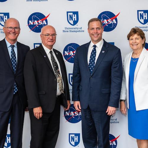UNH president, NASA head, EOS head, Senator Shaheen pose in front of UNH-NASA banner