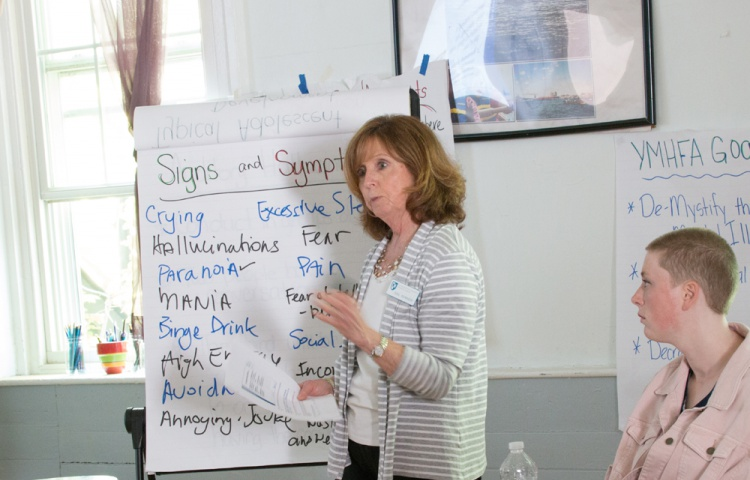 A woman leads a workshop on youth mental health challenges. she is standing in front of a chart; written on it are the words signs and symptoms. Underneath this title are signs and symptoms, including crying, fear, pain, binge drinking and others. The woman is addressing the audience. On the right side of the image, a participant in the workshop looks at the woman.