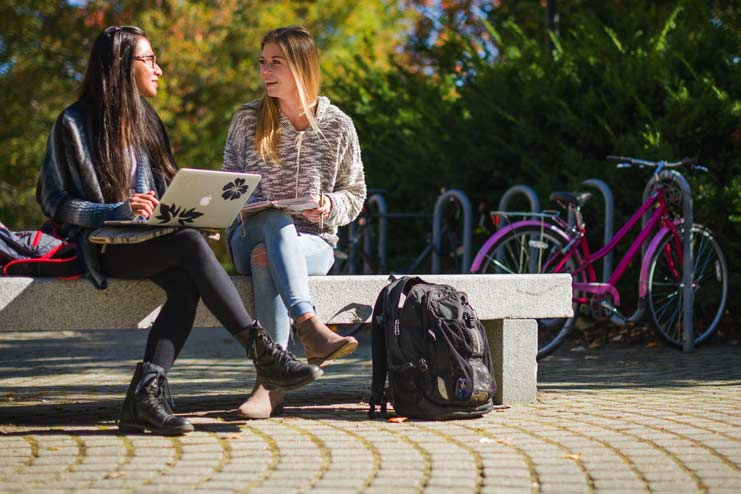 Two female students sitting on bench talking