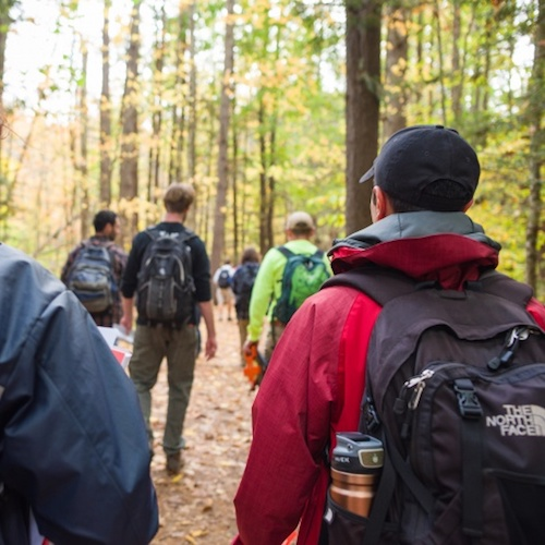 young people walking through woods wearing backpacks
