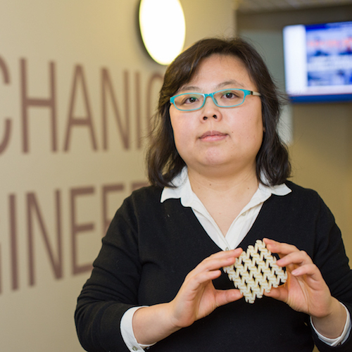 Researcher Yaning Li holding a small square model