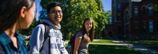 Three students walking and smiling on campus