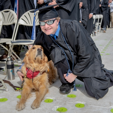 student with service dog at commencement
