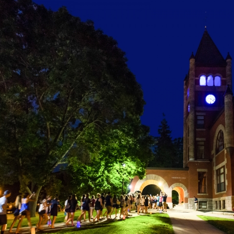 students walking under arch of Thompson Hall at night
