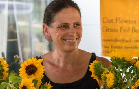 A woman farmer is standing and smiling behind her display of sunflowers