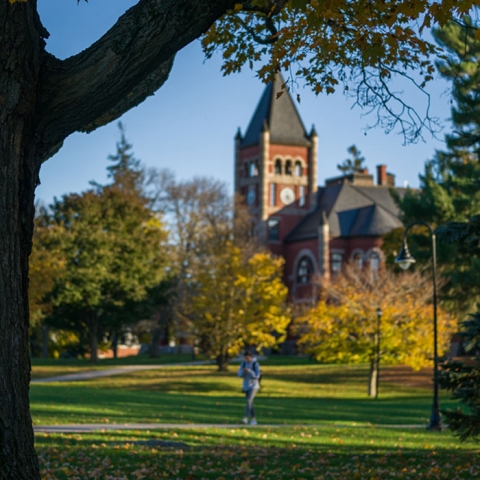 Thompson Hall in the fall with a student walking on the sidewalk