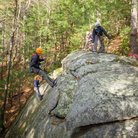 Students climbing on a large rock