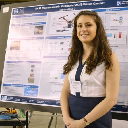 Female student standing in front of an undergraduate research board