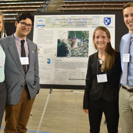 Two male and two female students standing in front of an undergraduate research board