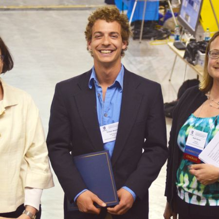 Smiling male student in between two women