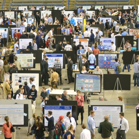 Frontal view of the URC floor with multiple people standing around in front of undergraduate research boards