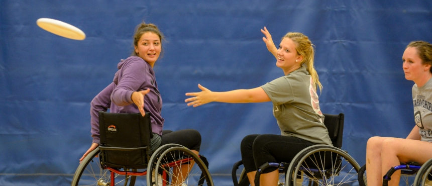 A photograph of students in wheelchairs playing ultimate frisbee in the gymnasium