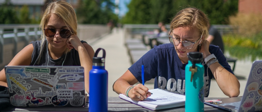 Two unh students sit studying outside on Durham campus with laptops at picnic table.