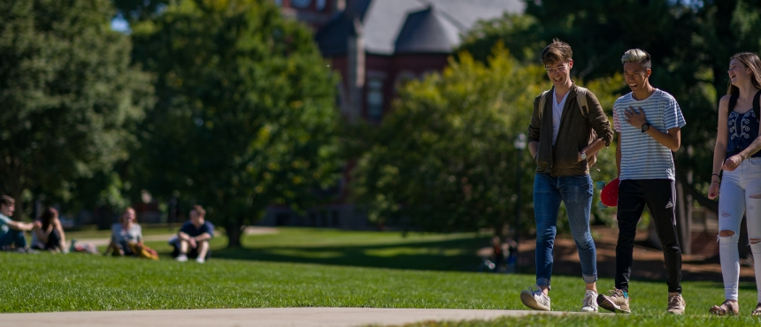 Students walk along campus path in front of Thompson Hall Durham campus.