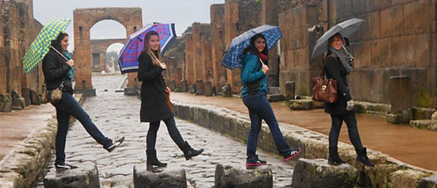 Side-view of four women standing on a different rock each, taking a step forward,  holding an umbrella.