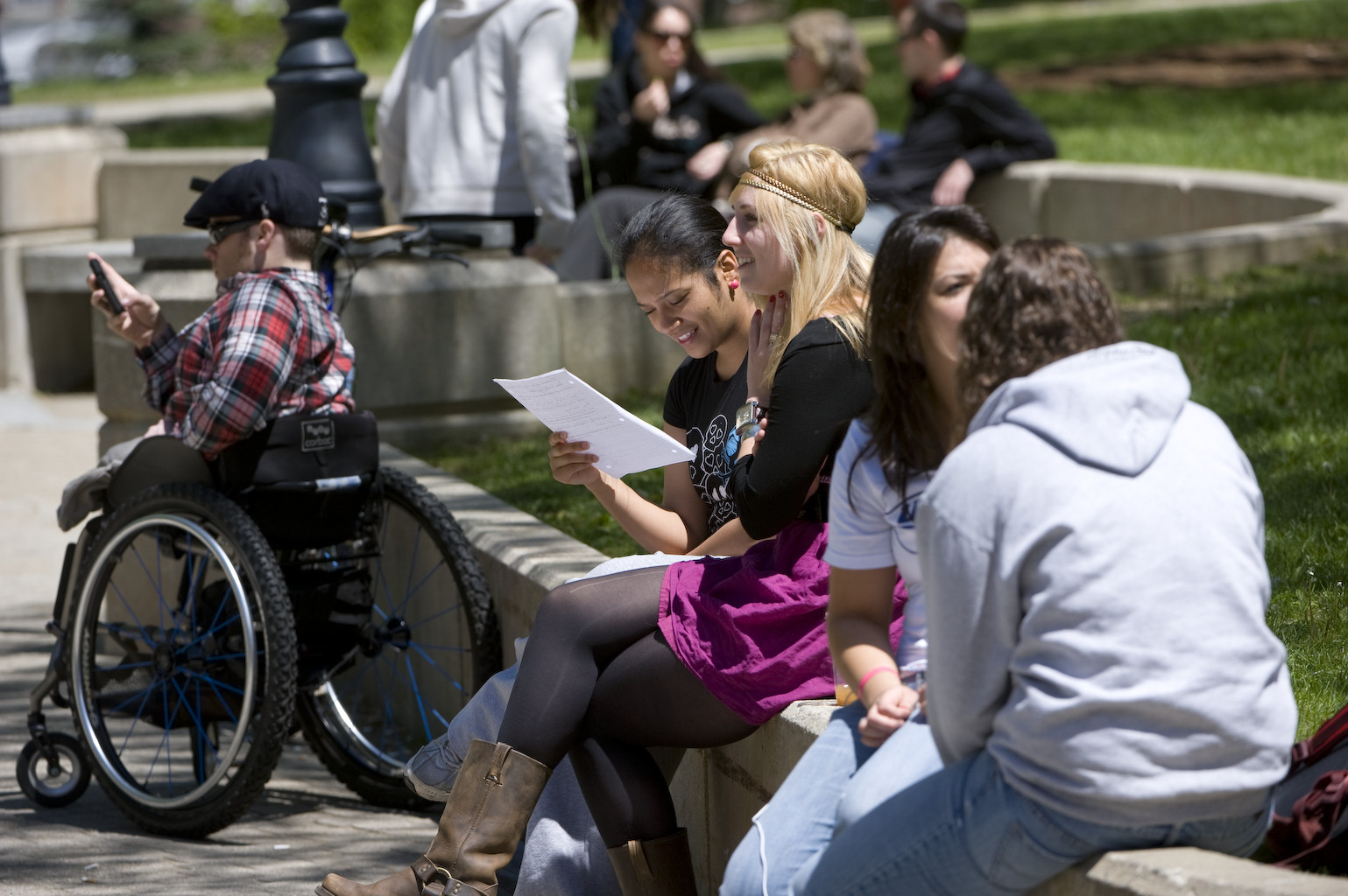 UNH students enjoy a sunny day. A student using a wheelchair is checking his phone.