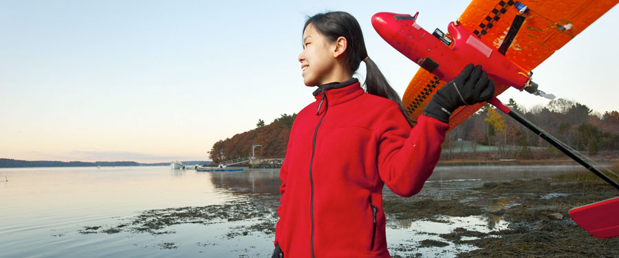 Female student holding small airplane.