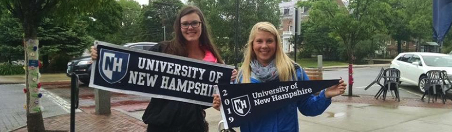 two students holding UNH Banners