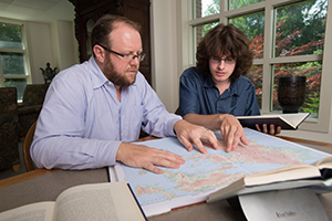 Professor and student look at map