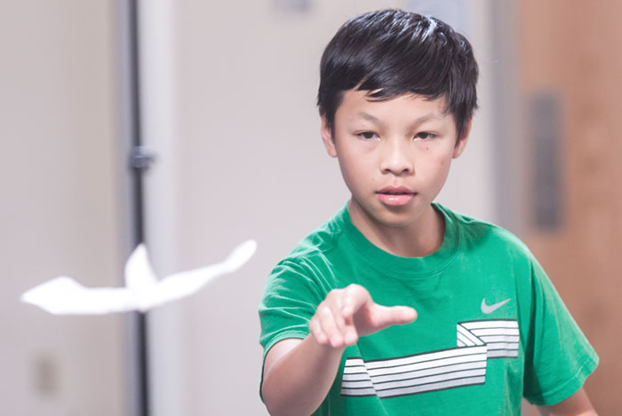 Child throwing paper airplane