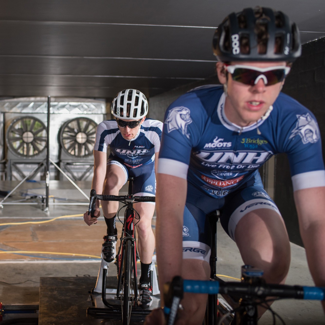 UNH undergraduate researchers on bicycles in the wind tunnel