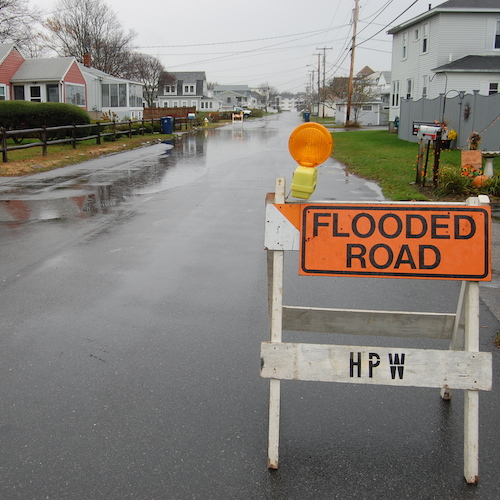 Flooded road with hazard sign