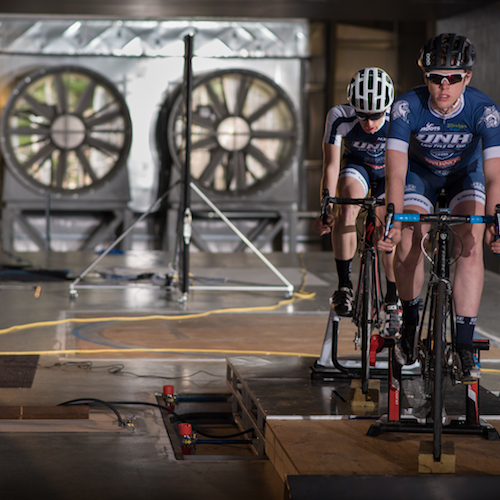 Two bicyclists in front of giant fans in wind tunnel