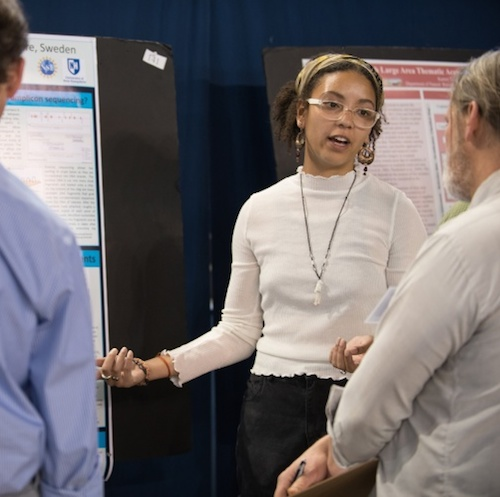 Young woman speaks to others in front of a research poster