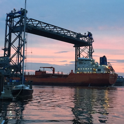 Tanker ship passes under Portsmouth's Memorial Bridge at sunset