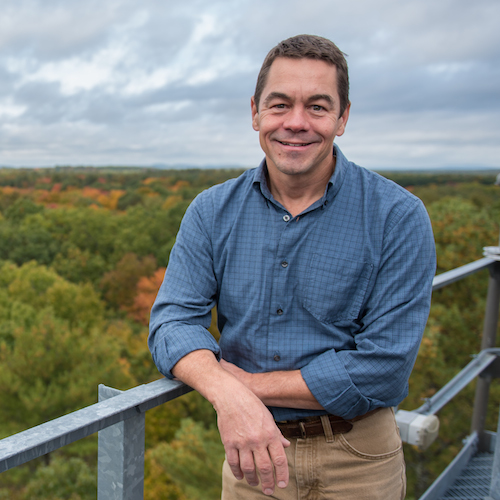 Researcher Scott Ollinger on a tower above a forest