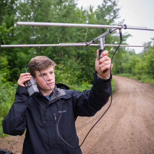 Student in the field holding antenna and tranceiver