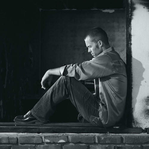 Black and white photo of casually dressed man sitting against a wall