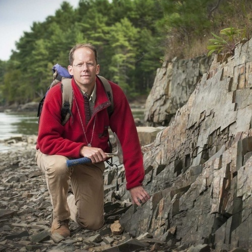 Geology professor Will Clyde kneels next to a rock face