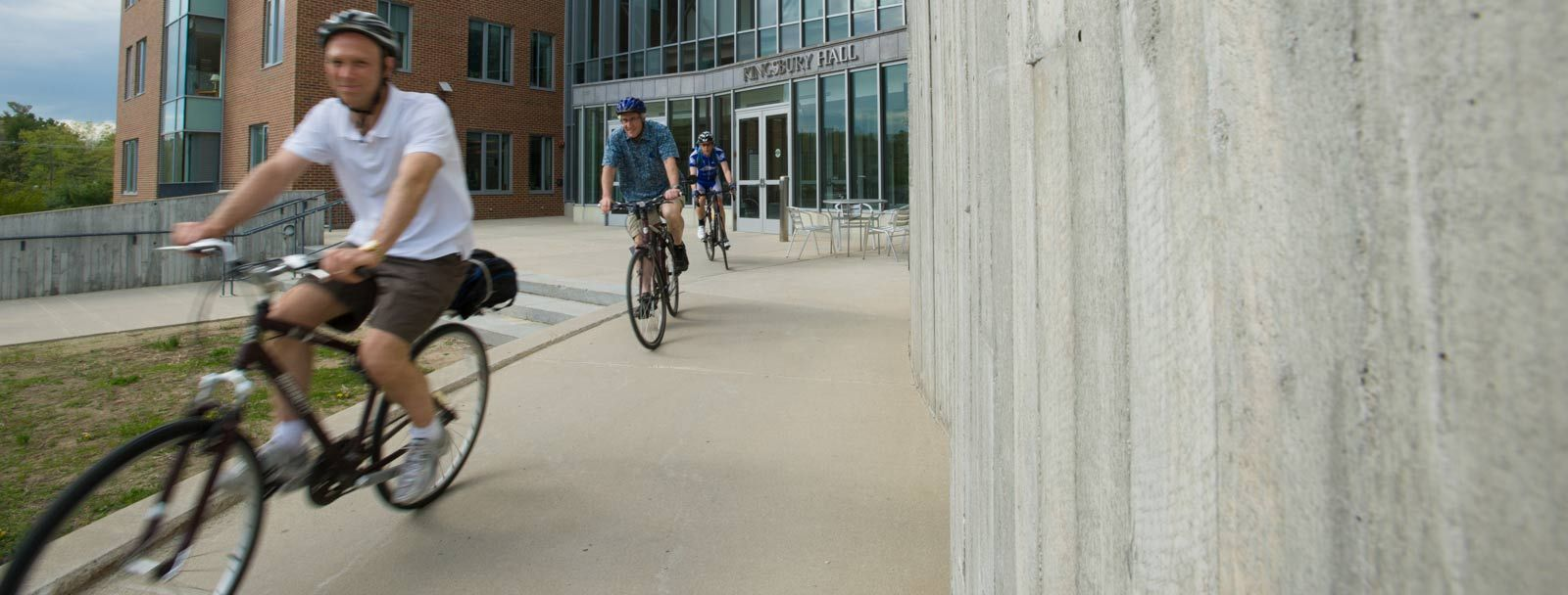 UNH faculty members leave Kingsbury Hall on bicycles