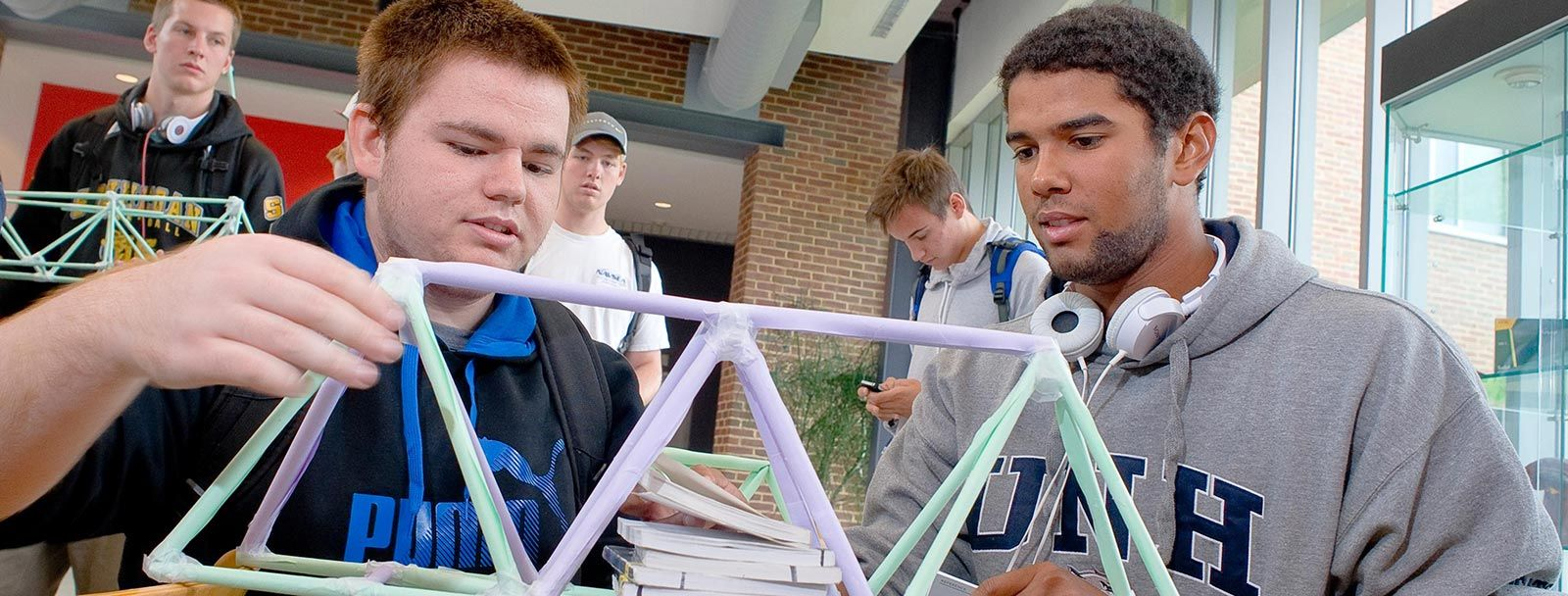 Two college-age male students build a bridge out of straws and tape