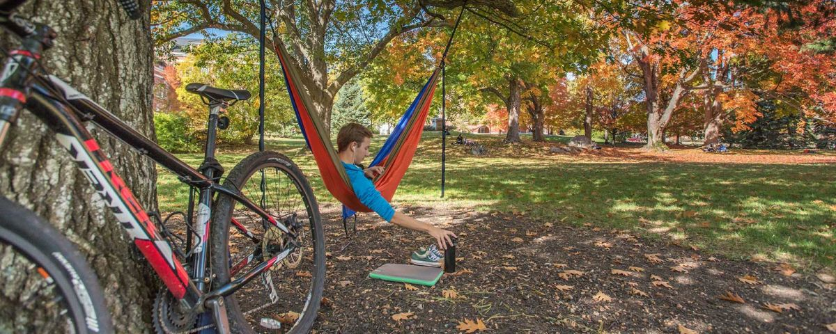 fall foliage and a student lounging in a hammock on the UNH campus in Durham, NH
