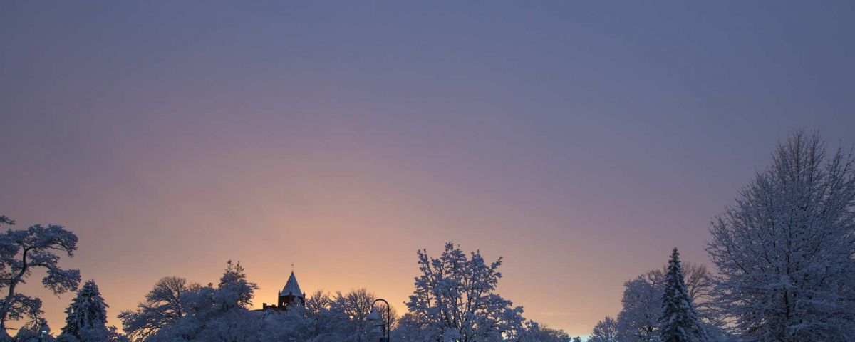 Sunset behind snow covered trees in front of Thompson Hall