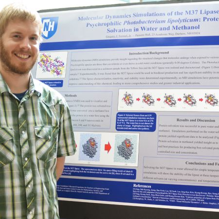 Male student standing in front of research board
