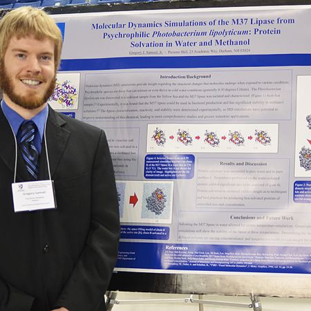 Male student standing in front of an undergraduate research board