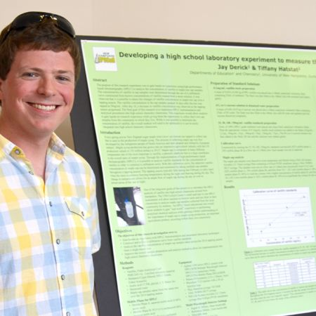 Male student standing in front of a research board