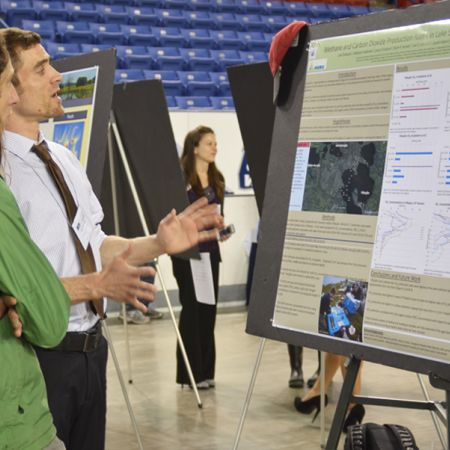 Two male students standing in front of an undergraduate research board, one demonstrating the research
