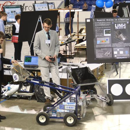 Two male students driving a four-wheeled robot with a remote controller